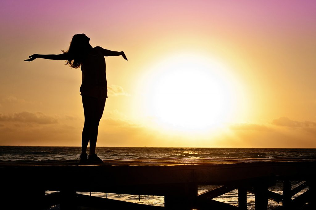 woman on beach with arms spread wide greeting sunrise